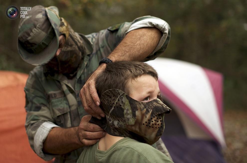 Наставник надевает маску на лицо своего сына перед началом полевых учений