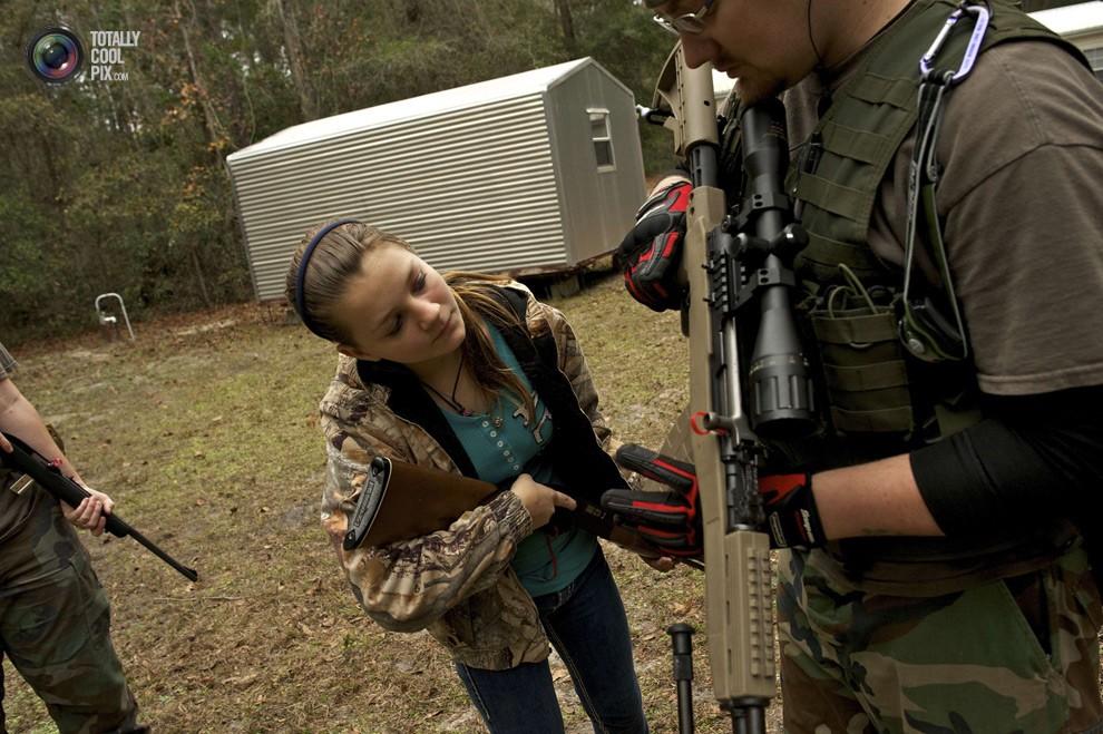 Один из членов группы объясняет девочке, как обращаться с карабином СКС-45