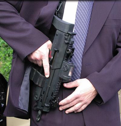 Пістолет кулемет HK MP7 (ймовірно) у швейцарського гвардійця особистої охорони понтифіка в костюмі фіолетового кольору.